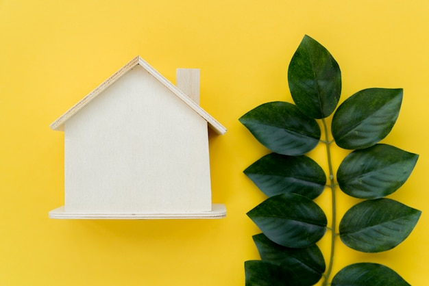 Wooden house model near the green leaves against yellow background