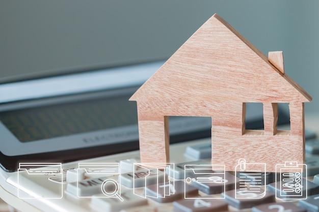 電卓の木造住宅モデル。デジタルドキュメントファイルのマーケティングアイコンを使用した不動産不動産抵当貸付または投資のアイデア。新しい家を購入することに合意するための計画管理の概念