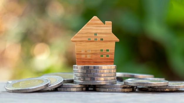 Модель деревянного дома на куче монет и затуманенном зеленом фоне природы, инвестициях в недвижимость и концепции жилищного кредита.