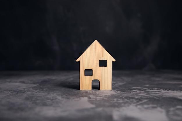 灰色のテーブルの背景に木造住宅モデル