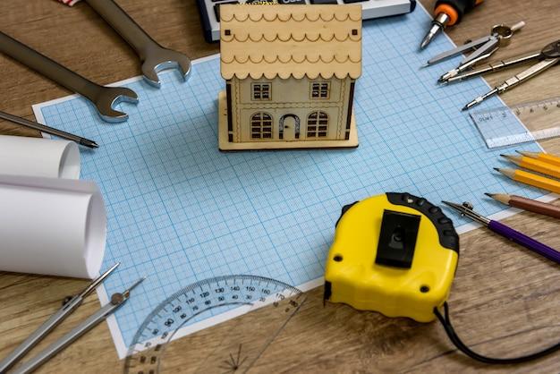 Модель деревянного дома на миллиметровой бумаге разными инструментами