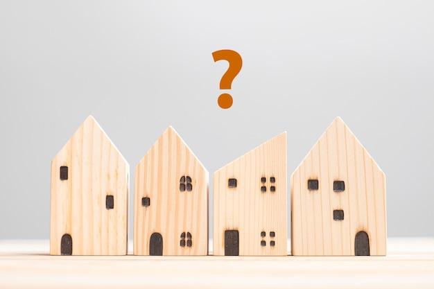 테이블 배경에 목조 주택 모델입니다. 가정, 위기, 경기 침체, 노숙자, 부동산, 구매 또는 임대 및 부동산 개념