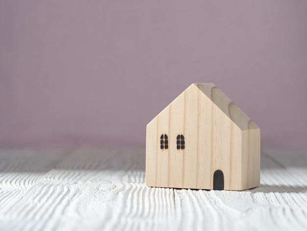 흰색 나무와 분홍색 배경에 목조 주택 모델. 주택 산업 모기지 계획 및 주거용 세금 절감 전략