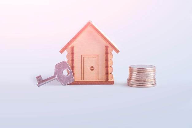 木造住宅モデル、青い背景にお金と鍵をストックします。住宅や不動産の売買の概念。住宅保険、不動産、住宅ローン。テキスト用のスペースをコピーする