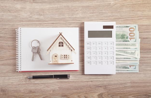 키, 계산기, 돈, 펜 및 메모장 목조 주택 모델.