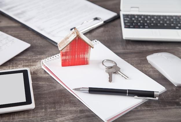 Модель деревянного дома с ключами, ручкой и блокнотом.