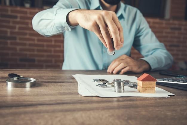 Модель деревянного дома с монетами или концепцией недвижимости
