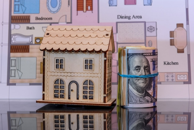 Wooden house model with dollar in roll with reflection