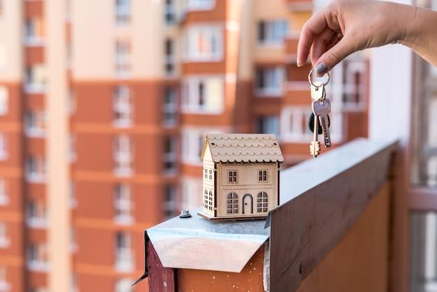 女性の手と鍵を持つ木造住宅モデル