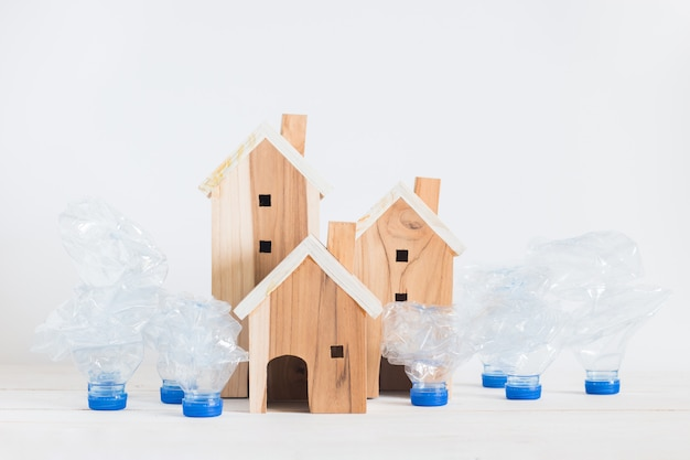 Wooden house model with garbage recycle plastic bottles setting on white wooden board, global warming solution.