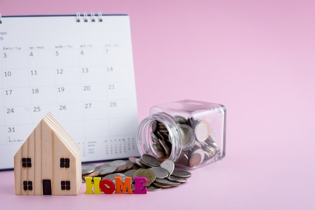 Wooden house model with home alphabet, money coins in the glass jar and calendar on pink background for housing business and planning concept