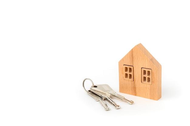 Модель деревянного дома с ключами на белом идолирует для концепции жилья и недвижимости