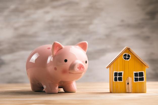 테이블에 돼지 저금통과 목조 주택 모델