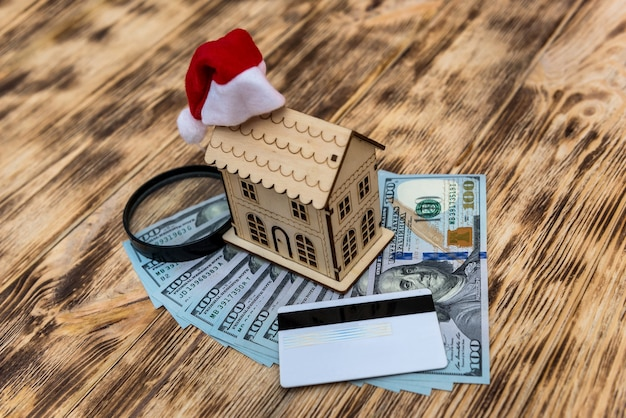 Wooden house model with santa hat and dollar banknotes