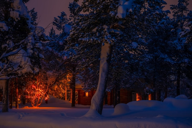 Wooden house in the night winter forest and christmas garland. a lot of snow