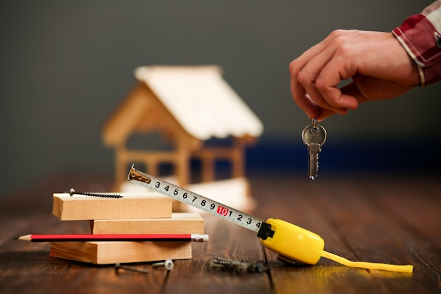 보드와 칩이있는 키의 무리에서 나무 표면에 목조 주택. 개념-턴키 주택 건설. 고품질 사진