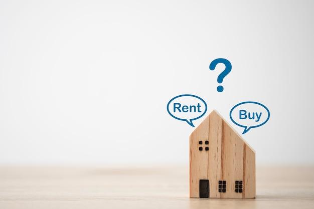 Деревянный дом на столе с надписью «арендовать» или «купить» и значок вопроса. это лучший выбор.