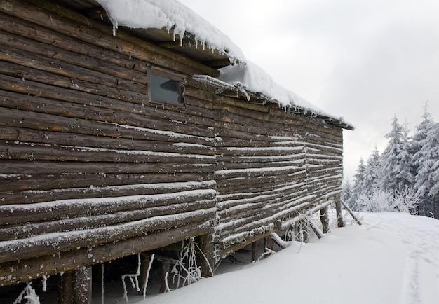Деревянный дом на вершине горы зимой