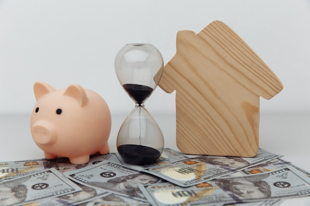 Wooden house, piggy bank and clock on dollar banknotes. investment.