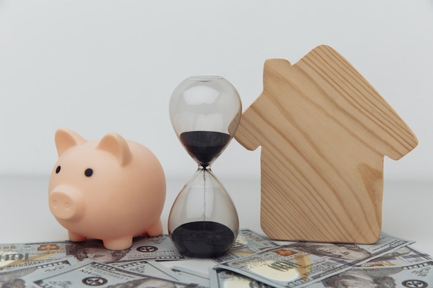 Wooden house piggy bank and clock on dollar banknotes