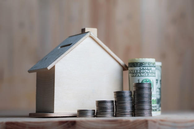 Wooden house piggy bank with dollar money and coin on wooden table over wood metaphor saving money for buy home and real estate
