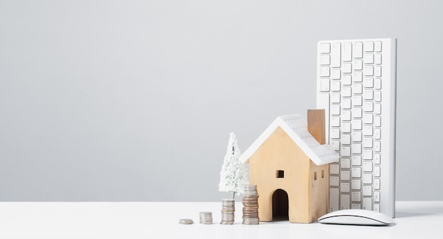 Wooden house and a pile of money coins working to save money to buy a house save for future ideas