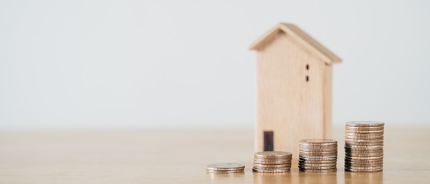 Wooden house and stacking coins on wooden table saving money for buying house home loan concept