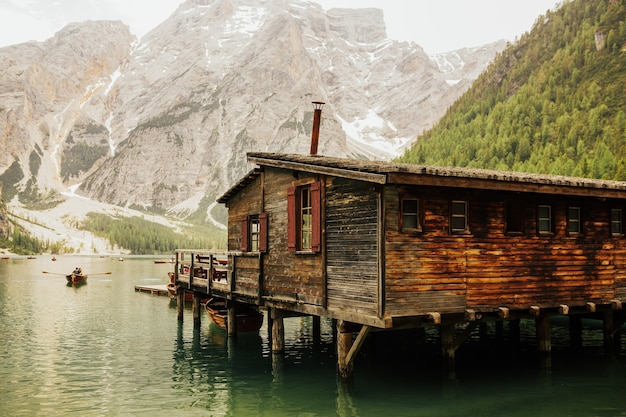 Wooden house in the summer day of the crystal clear water of lake braies in the dolomites, italy.