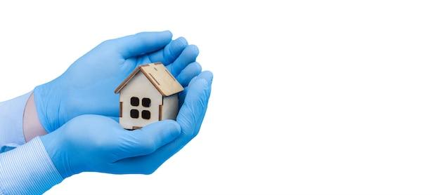 Деревянный дом в руки в медицинских перчатках. концепция защиты и профилактики заболеваний, баннер