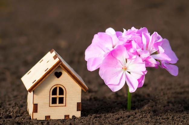 지상에 큰 분홍색 꽃을 가진 마음으로 목조 주택을 닫습니다.