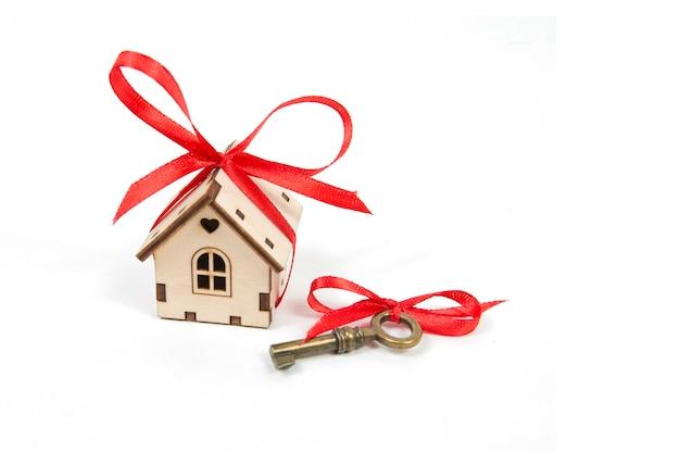 大きな赤い弓と白い壁に赤い弓が付いたヴィンテージの鍵が分離された、不動産購入コンセプトの木造住宅。