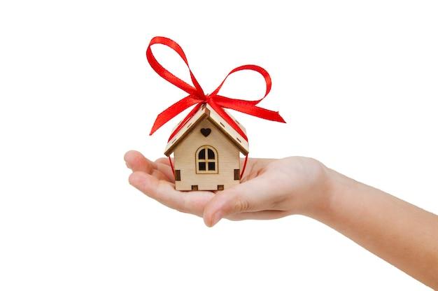 隔離された白い壁に大きな赤い弓を持つ木造住宅、ギフトとしてのコンセプト住宅