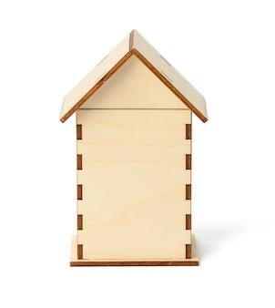 白い表面に隔離された屋根を持つ木造住宅。生態学的な子供のおもちゃ、クローズアップ