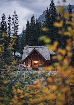 Wooden house with autumn leaves on emerald lake in yoho national park
