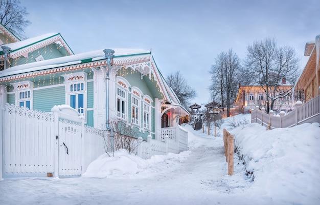 Деревянный дом с ажурными наличниками в плёсе в снегу в свете заходящего зимнего солнца