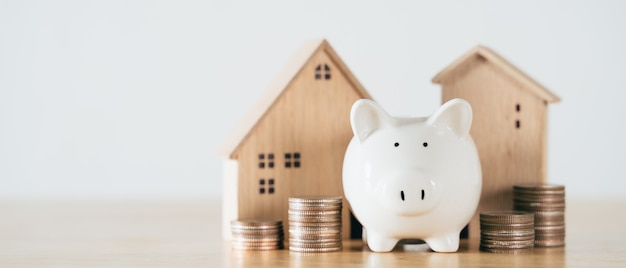 Wooden house with piggy bank and stacking coins on wooden table saving money for buying house
