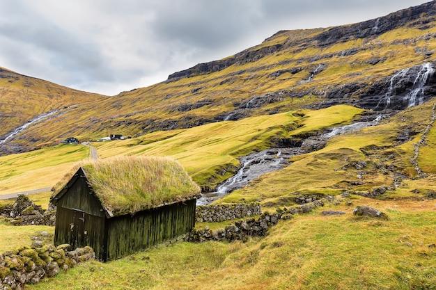 Деревянный дом с крышей из травы. деревня саксун и маленькие водопады, стреймой, фарерские острова