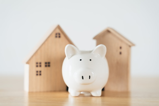 Wooden house with white piggy bank on wooden table saving money for buying house home loan