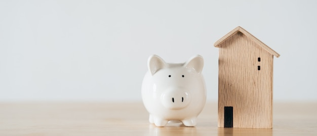 Wooden house with white piggy bank on wooden table saving money for buying house