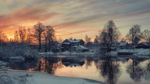 Wooden houses on the banks of the vuoksa river in the city of priozersk russia at sunrise in winter