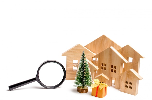 Wooden houses and christmas tree and magnifying glass.