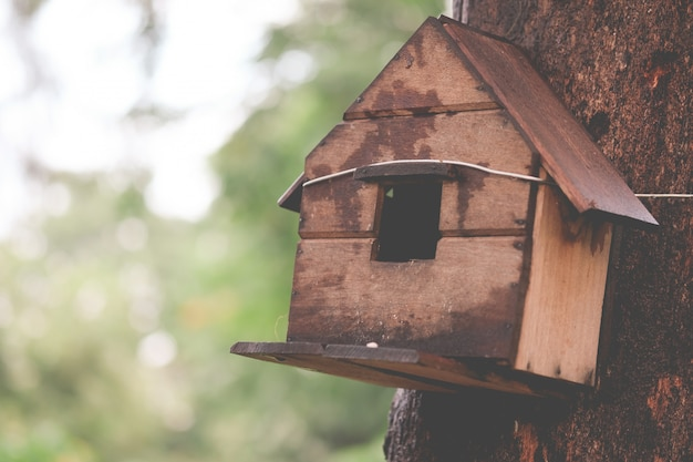 Wooden houses for little birds hanging on tree, vintage tone.