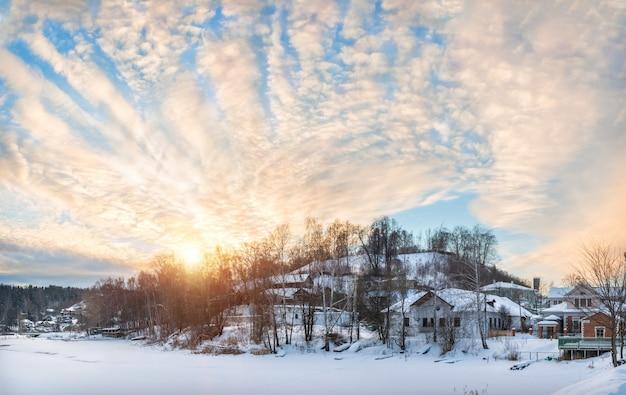 Деревянные дома на берегу заснеженной реки шохонки и соборной горы в плёсе в снегу в свете заходящего зимнего солнца