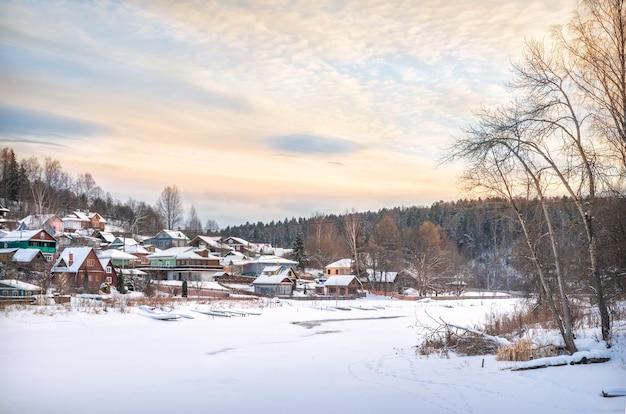 Деревянные дома на берегу заснеженной реки шохонка в плёсе в снегу в свете заходящего зимнего солнца