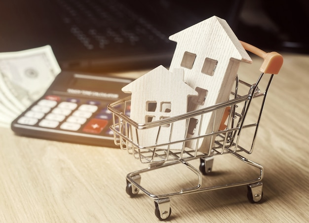 Wooden houses in a supermarket trolley, money and a calculator. real estate market analytics.