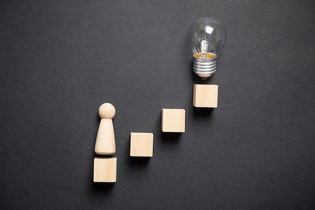 Wooden human figure with cubes and light bulb. idea