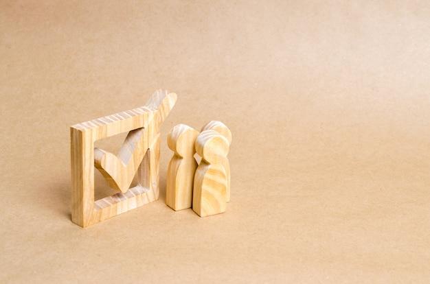 Рядом с галочкой в коробке стоят деревянные человеческие фигуры.