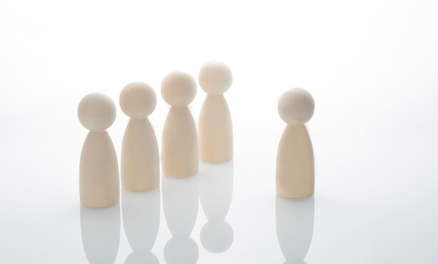 Wooden human figures on the white background. leader concept