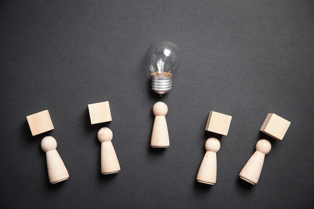 Wooden human figures with cubes and light bulb. idea