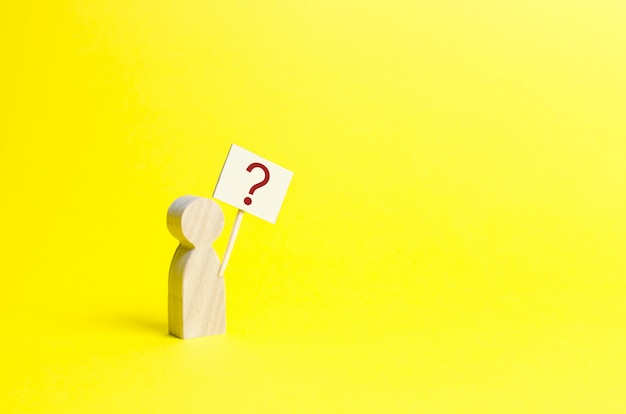 Wooden human figurine with a question mark
